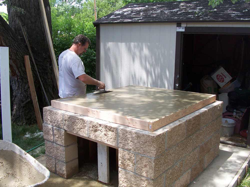 com laying the floor pad for a wood fired brick pizza oven